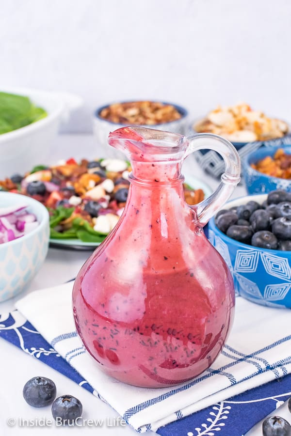 A glass jar filled with Creamy Blueberry Balsamic Salad Dressing with bowls of salad ingredients behind it