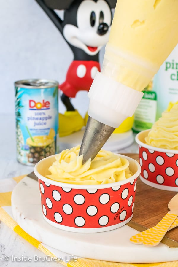 A piping bag with a star tip swirling Dole Whip into a red and white polkadot cup