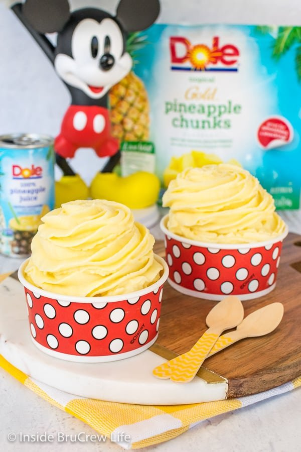Two red and white polkadot cups filled with Dole Whip swirls with a Mickey Mouse statue behind them