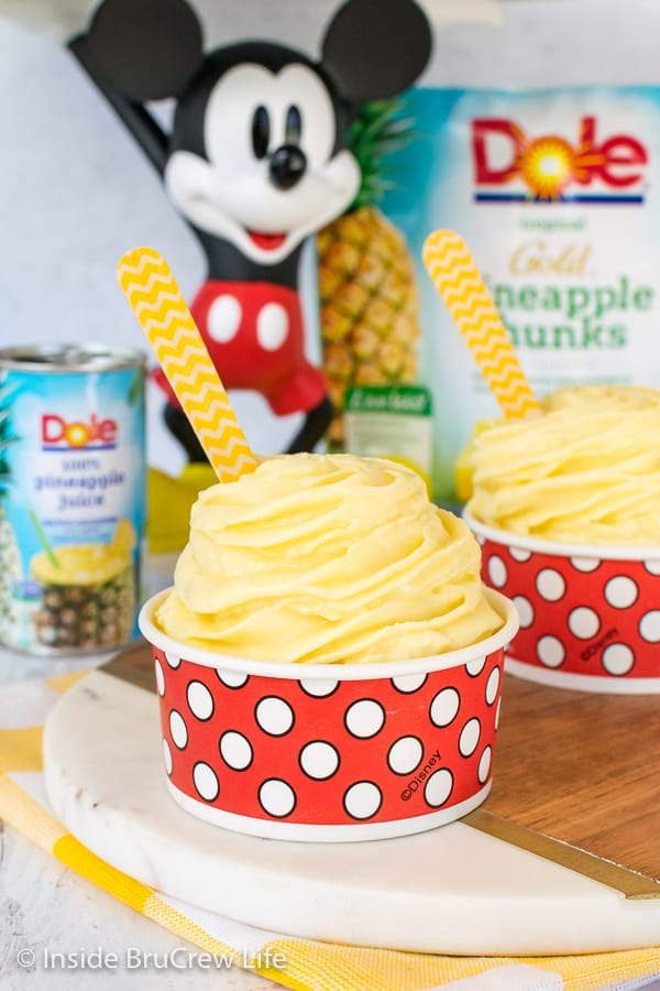 A red and white polkadot cup filled with a Dole Whip swirl and a yellow wooden spoon with Mickey Mouse behind it
