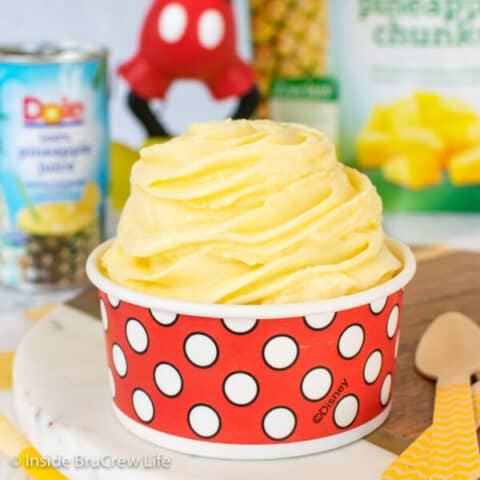 A red and white polkadot cup filled with a pineapple dole whip swirl in it