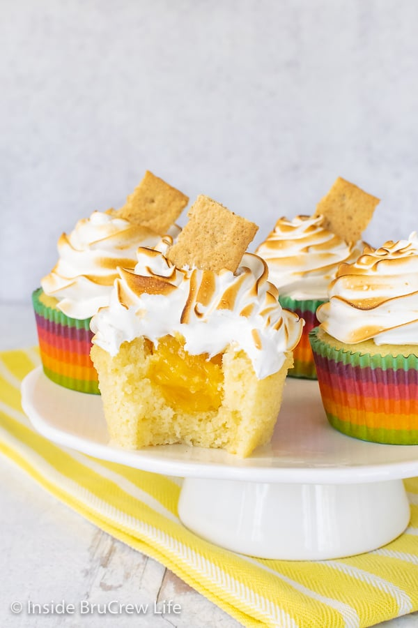 Four Lemon Meringue Cupcakes on a white cake plate with a yellow towel under it. One cupcake has a bite out of it showing the hidden lemon center.
