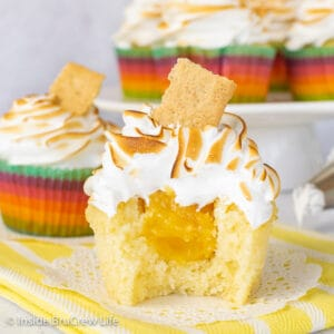 A close up picture of a lemon meringue cupcake on a white doily and yellow towel with a bite take out to show the hidden lemon center