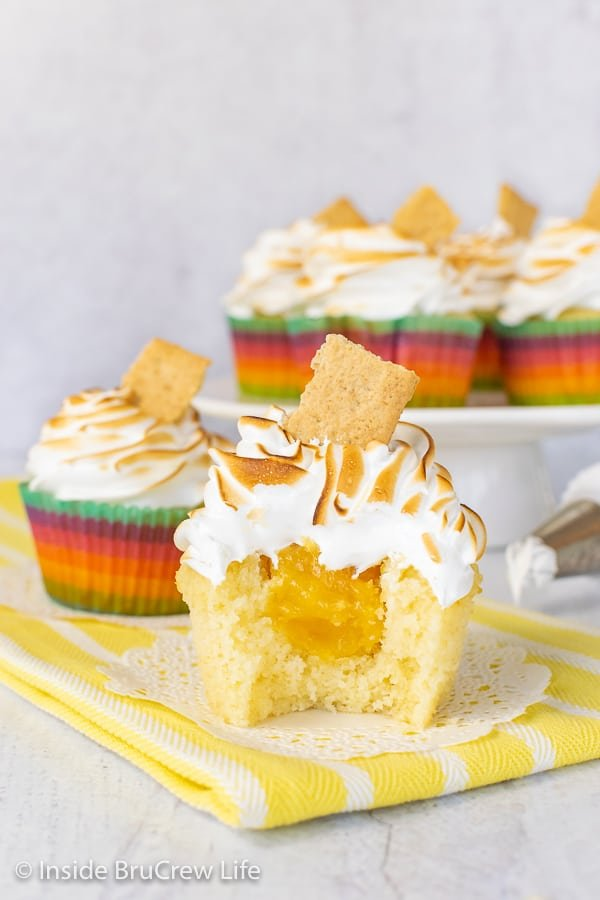Two lemon meringue cupcakes on white doilies with a bite out of the front cupcake showing the hidden lemon curd center and a cake plate with more cupcakes behind them