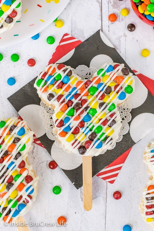 A close up overhead picture of a M&M's Mickey Mouse Rice Krispie Treat on a stick