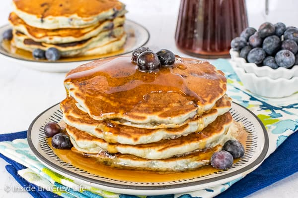 Four blueberry pancakes on a white plate with a few fresh blueberries on top and around the sides and drizzles of syrup on top