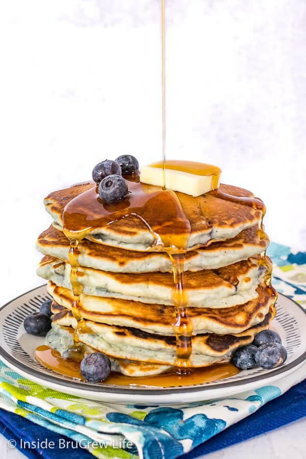 A stack of six blueberry pancakes on a white plate with a drizzle of syrup coming down over the top and sides