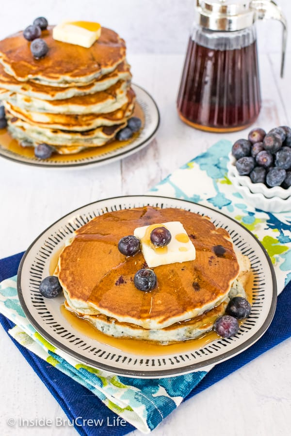 An overhead picture of two blueberry pancakes with butter and syrup on a white plate