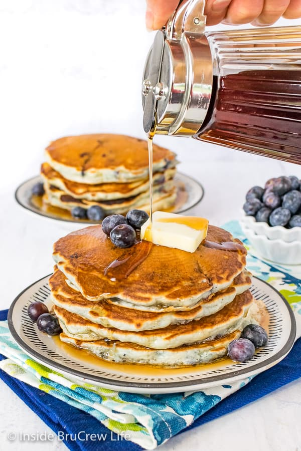 A stack of blueberry pancakes with a drizzle of maple syrup being poured on top
