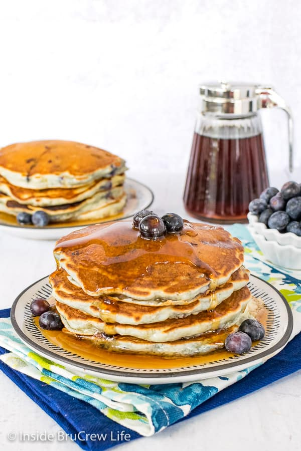 A stack of four blueberry pancakes on a plate with another plate of pancakes behind it