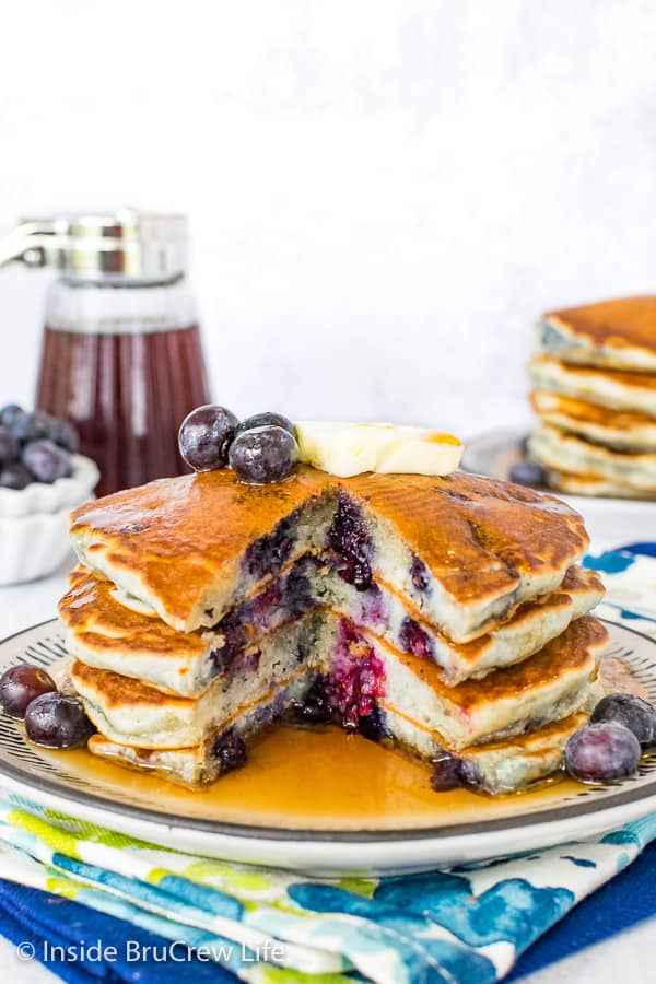 A stack of four blueberry pancakes on a plate with a section cut out showing the inside of the pancakes