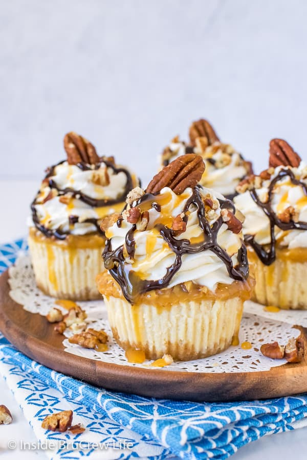 A brown wooden plate with four mini turtle cheesecakes topped with whipped cream and chocolate and caramel drizzles