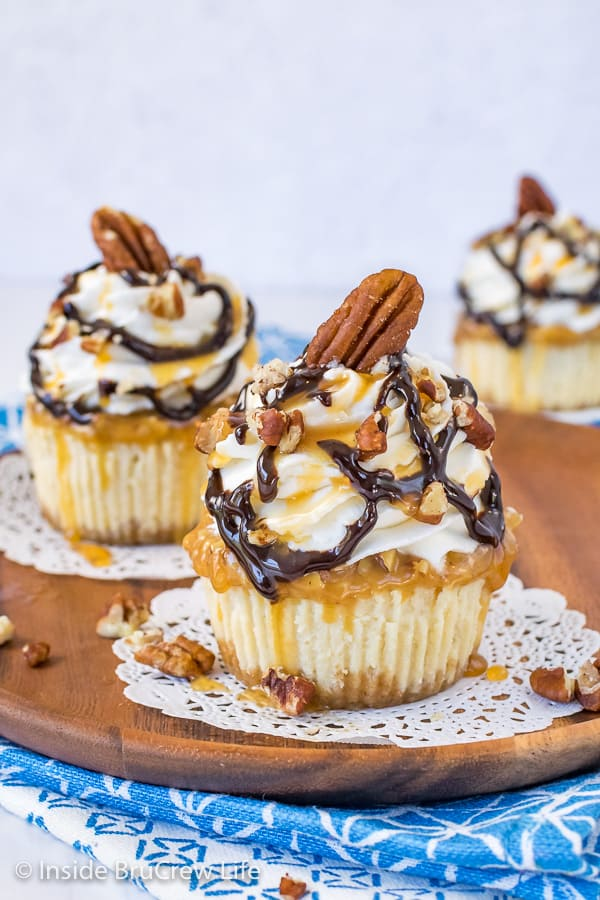 Two mini turtle cheesecakes topped with whipped cream and caramel and chocolate drizzles on a brown plate