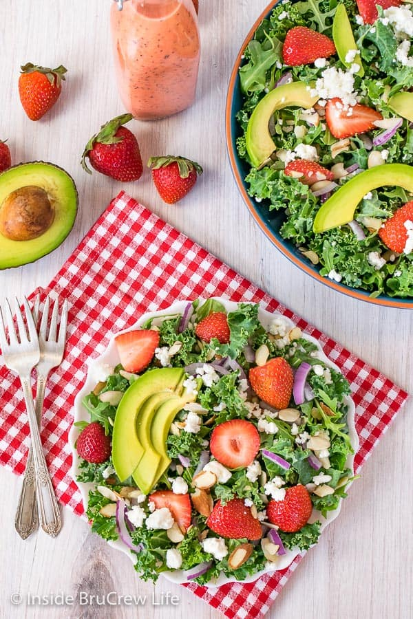 An overhead picture of a white plate filled with strawberry avocado salad and big bowl of salad beside it