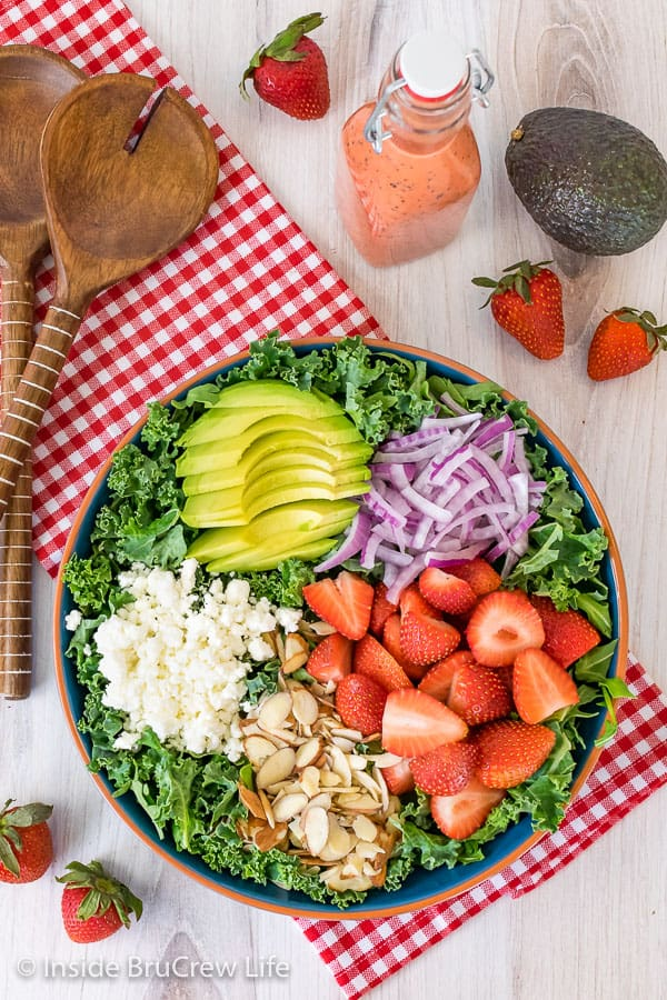 A large salad bowl on a red and white towel filled with kale and topped with avocados, onions, strawberries, nuts, and cheese