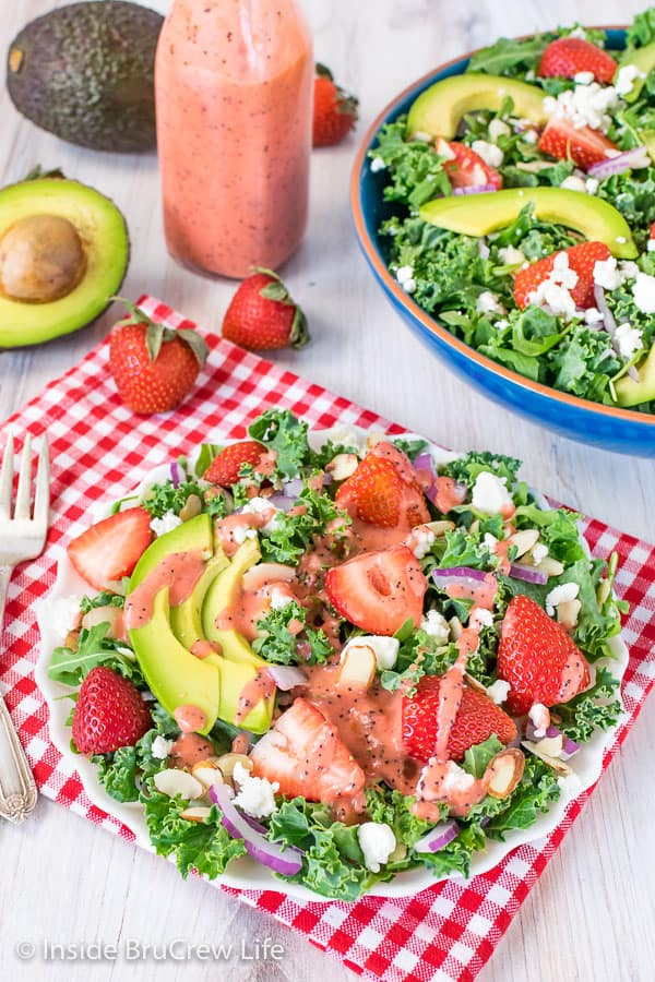 A white plate on a red and white checkered towel filled with strawberry avocado kale salad and drizzled with strawberry poppy seed dressing