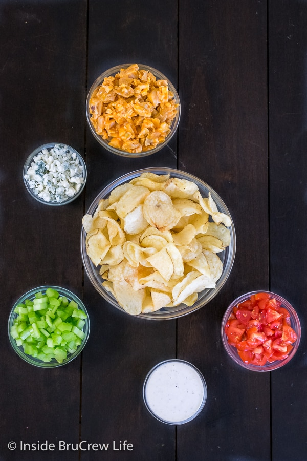 A dark background with bowls full of ingredients to make buffalo chicken chips