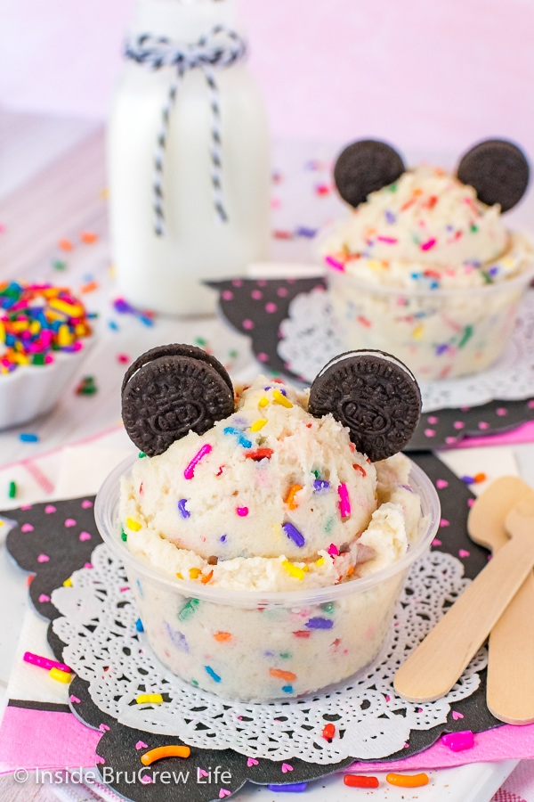 Two clear cups on white doilies filled with edible cookie dough that is loaded with colorful sprinkles and topped with chocolate cookies