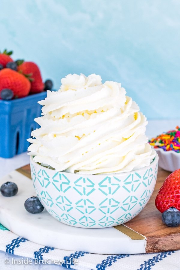 A white and green bowl filled with a big swirl of homemade whipped cream and berries behind it