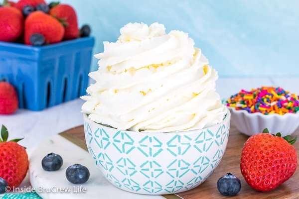 A bowl on a marble tray filled with a big swirl of homemade whipped cream and a box of berries behind it