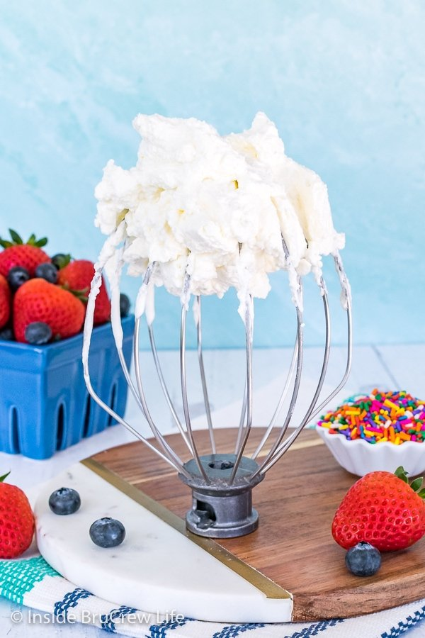 A whisk attachment standing upside down with fluffy homemade whipped cream on it