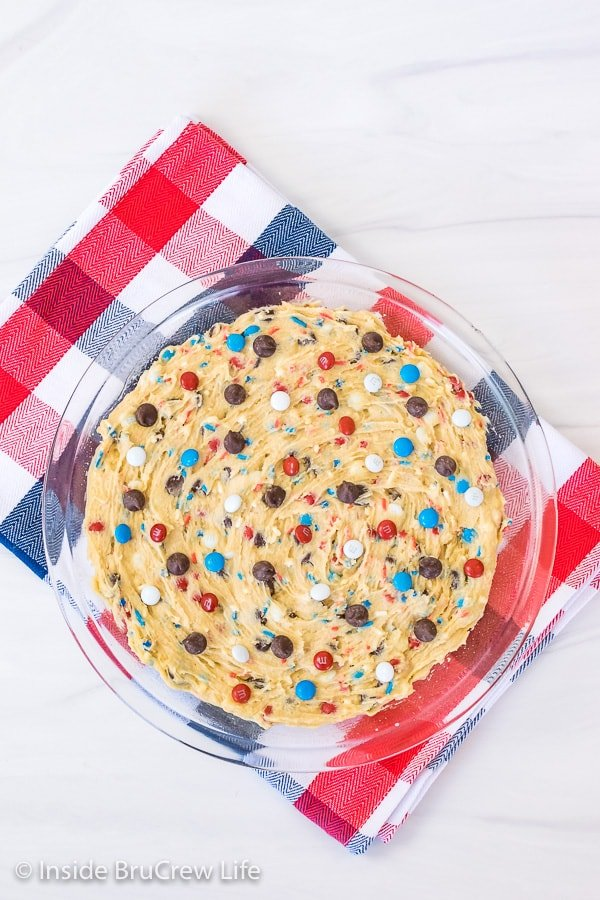 A pie plate on a red, white, and blue towel filled with chocolate chip cookie dough