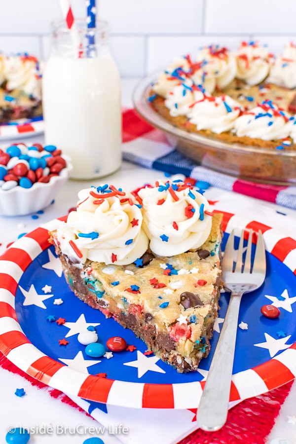 A red, white, and blue plate with a slice of chocolate chip cookie pie with frosting swirls and sprinkles on it