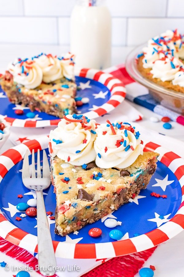 Two slices of patriotic chocolate chip cookie pie with frosting and sprinkles on red, white, and blue paper plates