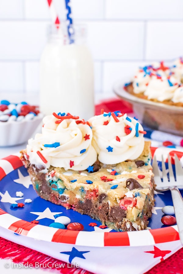 A red white and blue plate with a slice of chocolate chip cookie pie topped with swirls of frosting with patriotic sprinkles
