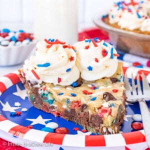 A red, white, and blue plate with a slice of chocolate chip cookie pie decorated with frosting swirls and sprinkles