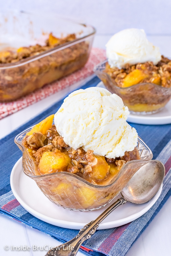 Two clear bowls on white plated with peach crisp and vanilla ice cream in them