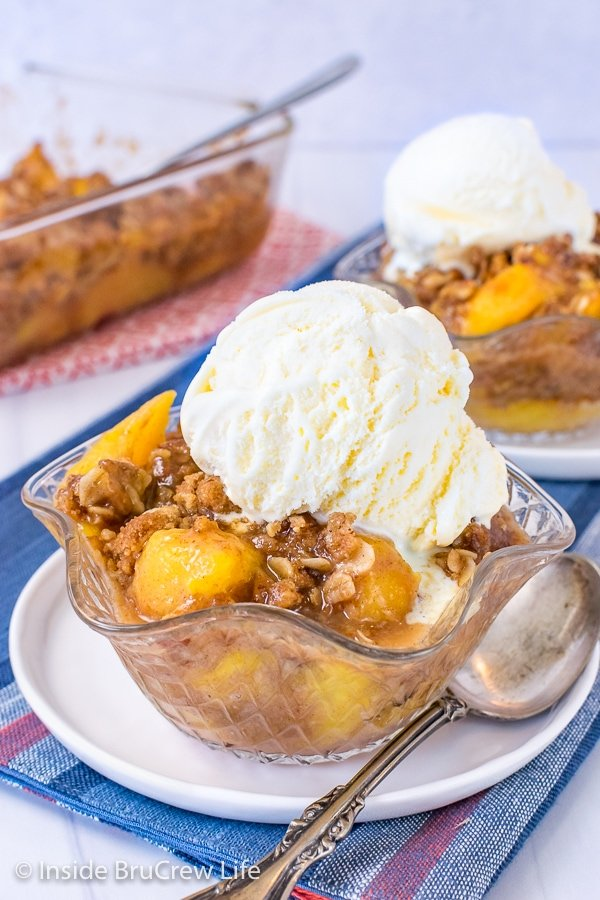 A clear bowl on a white plate filled with peach crisp and topped with vanilla ice cream