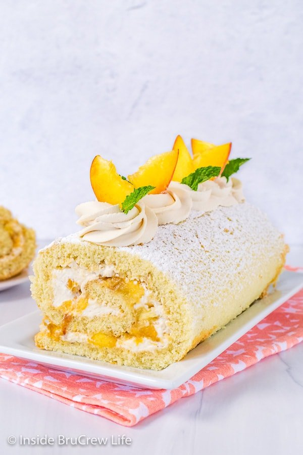 A white serving plate with a Peaches and Cream Cake Roll on it decorated with whipped cream swirls and fresh peach slices