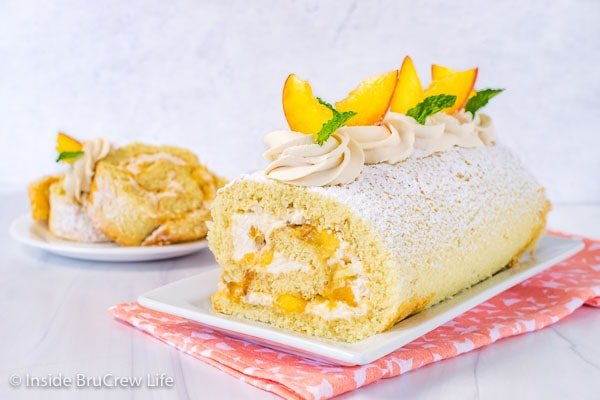 A white plate with a peaches and cream cake roll on it decorated with whipped cream swirls and fresh peach slices