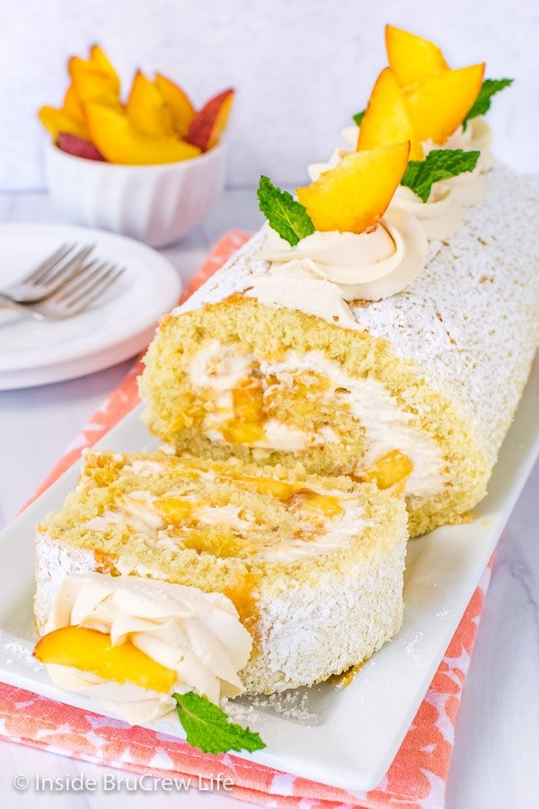A peaches and cream cake roll on a white plate with one slice flipped down