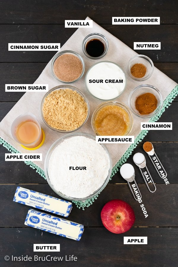 A wooden board with bowls of ingredients needed to make apple cider donut holes.