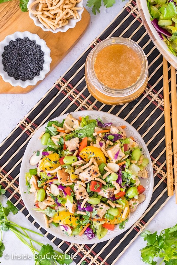 Overhead picture of an asian chicken salad on a white plate and black placemat