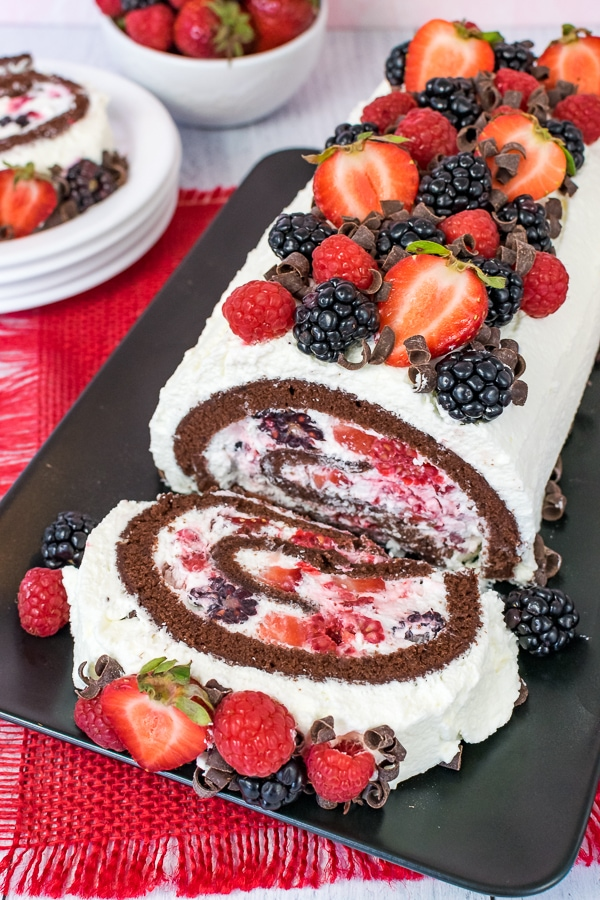 Overhead picture of a berries and cream chocolate cake roll on a black plate with one slice flipped down so you see the cream and berry filling.