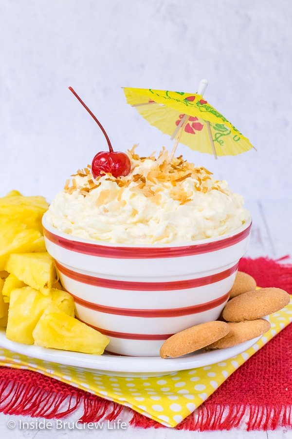 A white bowl with red striped filled with pina colada fruit dip and surrounded with pineapple wedges and vanilla wafers