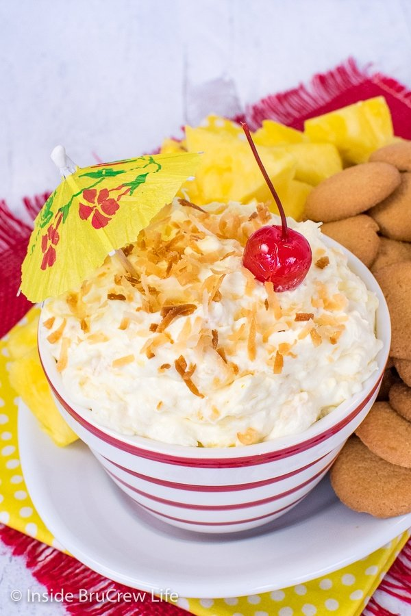 Close up picture of the top of a bowl filled with pina colada fruit dip and topped with toasted coconut and a cherry