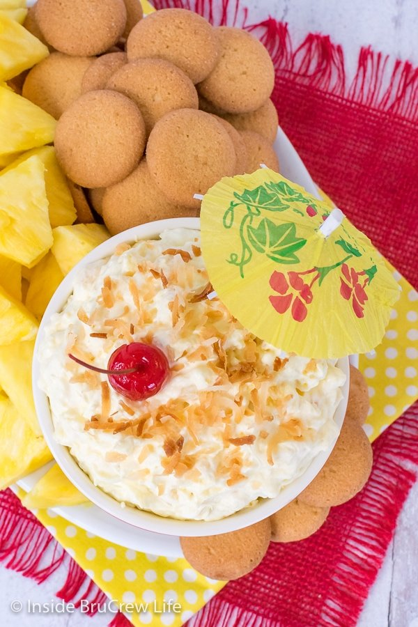 Overhead picture of a bowl of pina colada fruit dip on a plate with vanilla wafers and pineapple wedges