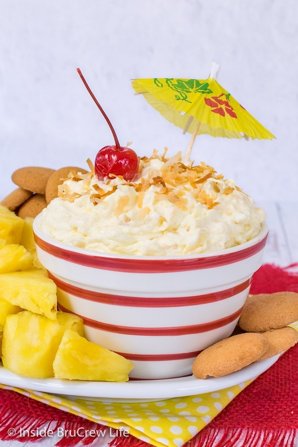 A red and white striped bowl filled with pina colada fruit dip and pineapple wedges and vanilla wafers around it