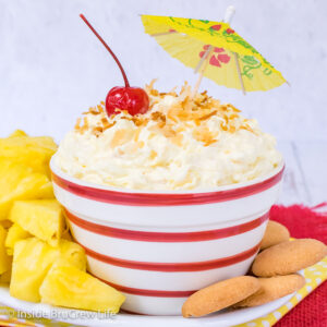 A red and white striped bowl filled with pina colada fruit dip