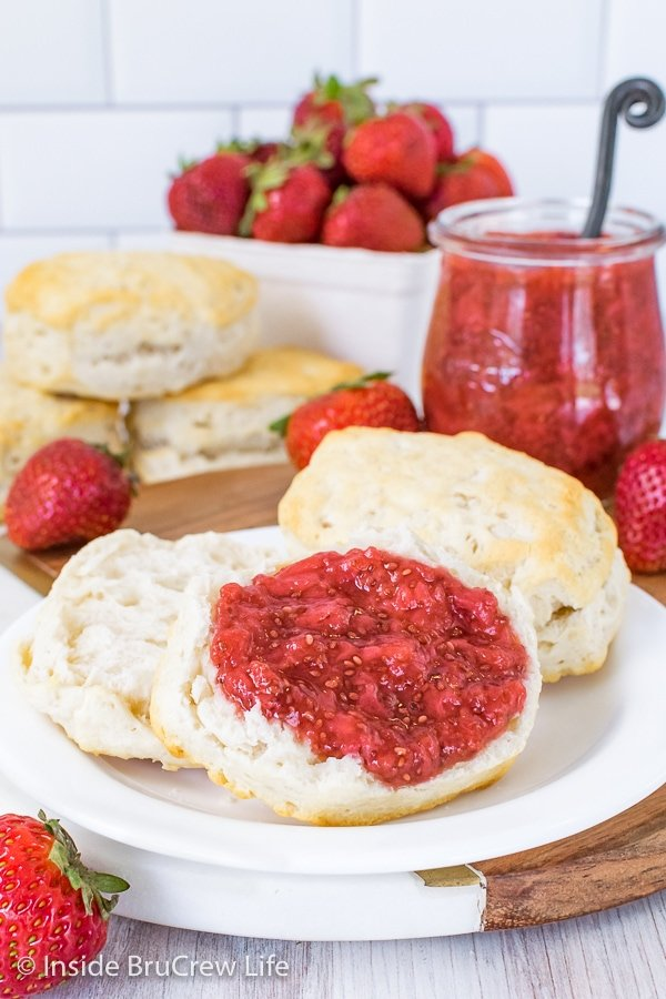 An open biscuit on a white plate with strawberry chia jam on it and a jar of jam behind it