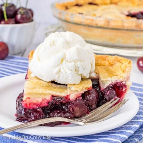 A white plate with a fork and a slice of cherry pie topped with vanilla ice cream