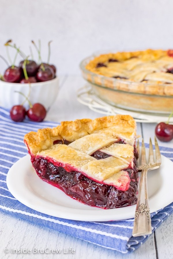 A white plate with a fork and a slice of cherry pie on it