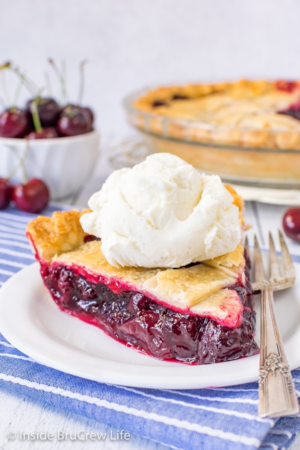 A slice of cherry pie with vanilla ice cream on a white plate