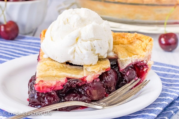 A white plate with a slice of cherry pie topped with vanilla ice cream on it