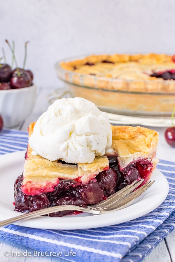 A white plate with a fork and a slice of cherry pie with vanilla ice cream on top