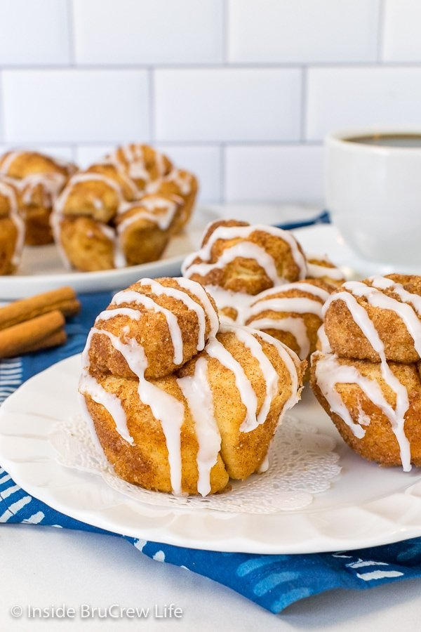 A white plate with three monkey bread muffins drizzled with glaze on it